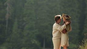 Mooie meermin in bloemkroon en jonge mens in liefde Magisch paar die op achtergrond van oude groene geheimzinnigheid omhelzen stock video