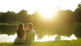 Mooie meisje en jongen die zonsondergang van zitting op het groene gras genieten dichtbij het meer Achtermening van gelukkig paar stock footage