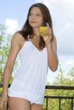 Mooie meisje het drinken ochtendsinaasappel op balkon Stock Afbeeldingen