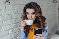 Mooie meisje het drinken thee en het werken met telefoon Stock Fotografie