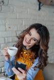 Mooie meisje het drinken thee en het werken met telefoon Stock Afbeelding