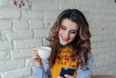 Mooie meisje het drinken thee en het werken met telefoon Royalty-vrije Stock Foto