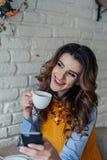 Mooie meisje het drinken thee en het werken met telefoon Stock Afbeeldingen