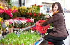 Mooie meisje het kopen bloemen Stock Afbeelding