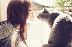 Mooie meisje het kussen kat Stock Afbeeldingen
