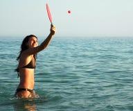 Mooie meisje het spelen bal in de oceaan royalty-vrije stock afbeelding