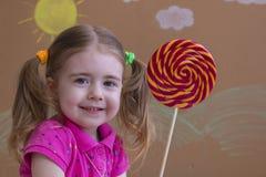 Mooie meisjeglimlachen met lolly, gelukkig meisje die grote suikerlolly eten Stock Foto's