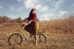 Mooie meisjes berijdende fiets op gebied Stock Fotografie
