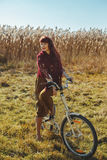Mooie meisjes berijdende fiets op gebied Stock Foto's