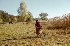 Mooie meisjes berijdende fiets op gebied Stock Afbeelding