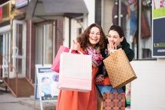 Mooie meisjes die met pakketten terwijl het winkelen lachen Stock Afbeeldingen
