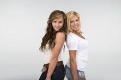 2 mooie meisjes die tegen een witte achtergrond glimlachen Royalty-vrije Stock Foto