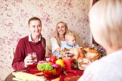Mooie meisjes en babyjongenszitting bij de feestelijke lijst aangaande een huisachtergrond Familie die bij Kerstmisdiner glimlach Royalty-vrije Stock Afbeeldingen