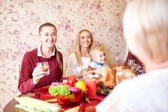 Mooie meisjes en babyjongenszitting bij de feestelijke lijst aangaande een huisachtergrond Familie die bij Kerstmisdiner glimlach Royalty-vrije Stock Afbeelding