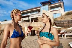 Mooie meisjes in het swimwear glimlachen, het drinken sap op zee strand Stock Afbeeldingen