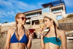 Mooie meisjes in het swimwear glimlachen, het drinken sap op zee strand Stock Foto's