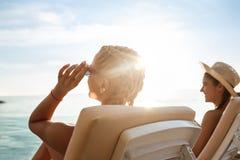 Mooie meisjes in het swimwear zonnebaden, die op chaises dichtbij overzees liggen Royalty-vrije Stock Foto