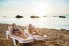 Mooie meisjes in het swimwear zonnebaden, die op chaises dichtbij overzees liggen Stock Foto's