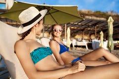 Mooie meisjes in het swimwear zonnebaden, die op chaises dichtbij overzees liggen Stock Fotografie