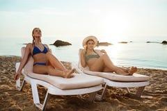 Mooie meisjes in het swimwear zonnebaden, die op chaises dichtbij overzees liggen Royalty-vrije Stock Foto's
