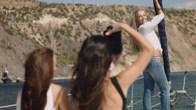 Mooie meisjes met camera op het jacht Royalty-vrije Stock Afbeeldingen