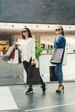 Mooie meisjes met document zakken in een zaal van een winkelcomplex stock afbeelding