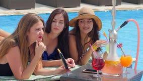 Mooie meisjes met gekleurde drankroddel dichtbij Zwembad stock footage