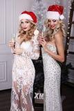Mooie meisjes met het blonde haar stellen naast Kerstboom stock afbeeldingen