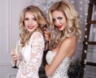Mooie meisjes met het blonde haar stellen naast Kerstboom royalty-vrije stock foto's
