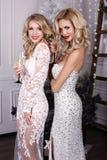 Mooie meisjes met het blonde haar stellen naast Kerstboom royalty-vrije stock afbeeldingen