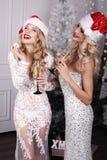Mooie meisjes met het blonde haar stellen naast Kerstboom royalty-vrije stock fotografie