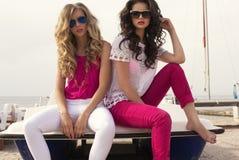 Mooie meisjes met zonnebril die op de zomerstrand stellen Stock Foto's