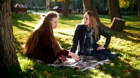 Mooie meisjes in parkzitting op algemeen en het spreken aan elkaar in mooi zonlicht stock video