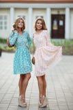 Mooie meisjes in roze en blauwe bloemrijke en kleding die stellen glimlachen royalty-vrije stock afbeeldingen