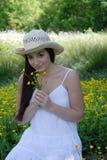 Mooie meisjes ruikende boterbloemen Royalty-vrije Stock Afbeeldingen