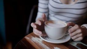 Mooie meisjes` s handen en een kop van koffie stock videobeelden