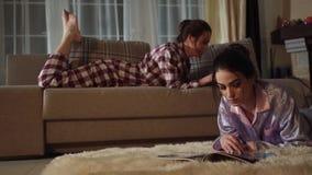 Mooie meisjes in slaapkostuums De één meisjesdrukken op een cel terwijl het zitten op een bank, tweede ligt op de vloer stock videobeelden