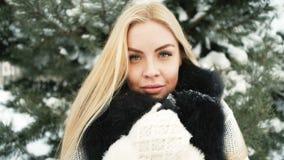 Mooie meisjesglimlachen tegen achtergrond van sneeuw behandeld bos stock videobeelden