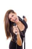 Mooie meisjesholding microfoon en zingen luid in zwarte dres stock fotografie