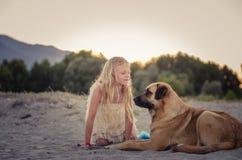 Mooie meisjeskind en hond in zandig strand stock afbeeldingen