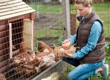 Mooie meisjeslandbouwer die verse eieren verzamelen in mand bij kippenlandbouwbedrijf in platteland stock afbeelding
