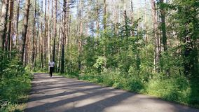 Mooie meisjeslooppas op een bosweg stock video
