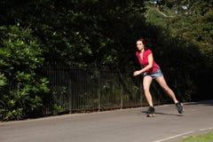Mooie meisjesrol die met lange benen in park schaatst stock foto