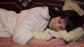Mooie meisjesslaap in bed die haar hoofdkussen koesteren stock video