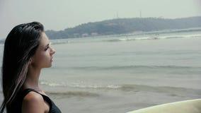 Mooie meisjessurfer of mooie vrouw, sexy slank brunette, in zwempak met sexibillen die gele surfplank houden stock video