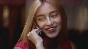 Mooie meisjeszitting dichtbij het venster en het spreken op haar mobiele telefoon bij de koffie stock video