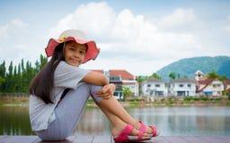 Mooie meisjeszitting dichtbij natuurlijke vijver met woonwijk stock foto