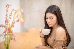 Mooie meisjeszitting in een koffie stock foto's