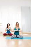 Mooie meisjeszitting in Lotus-positie met het bidden hand Stock Foto's