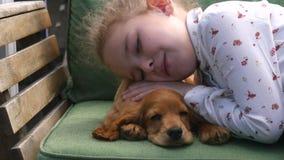 Mooie meisjeszitting met haar puppy op de bank stock footage
